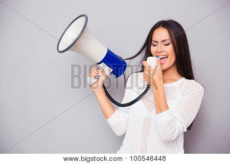 Portrait of a casual beautiful woman screaming on megaphone over gray background