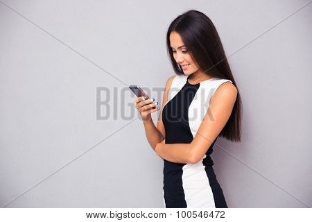 Portrait of a smiling woman in dress using smartphone on gray background