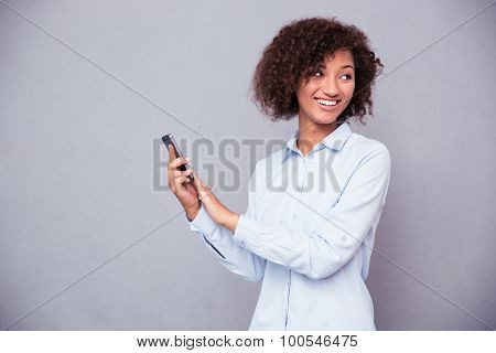 Portrait of a smiling afro american businesswoman using smartphone on gray background