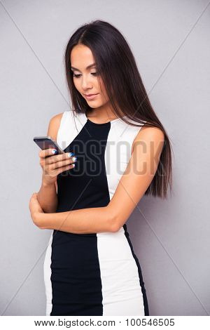 Portrait of a cute woman using smartphone on gray background