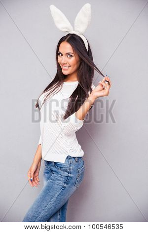 Portrait of a happy pretty woman in bunny ears looking at camera over gray background