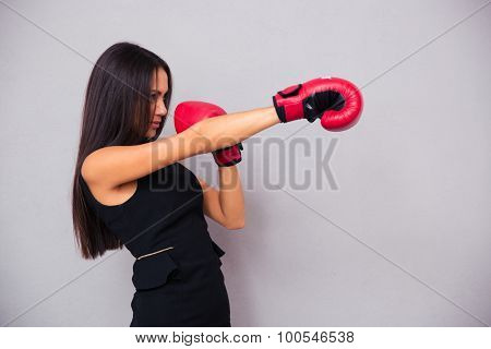 Side view portrait of a businesswoman fighting in boxing gloves on gray background