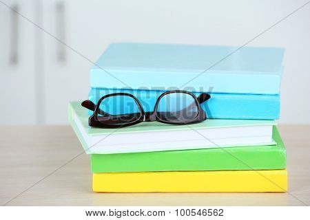 Stack of books with glasses on wooden table in room, closeup