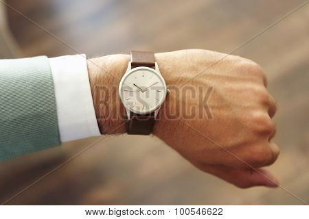 Businessman looking at his watch in office