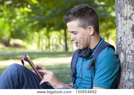 Smart boy using a tablet computer outdoors