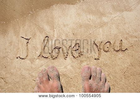 Conceptual love you handwritten text in sand on a beach in an exotic island with feet