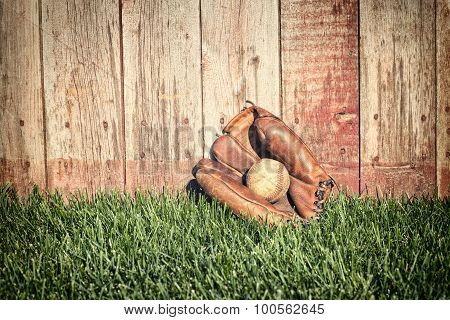 Old Baseball Mitt And Ball On Grass Against Wooden Fence