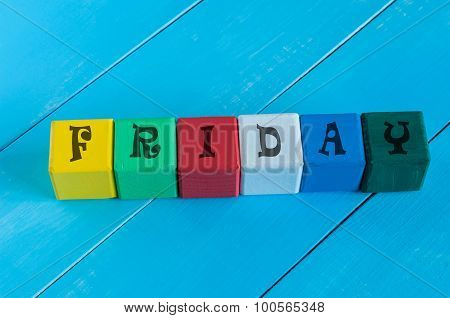 Friday - word written in child's color wooden cubes, on light blue wood background.