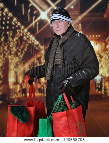 Image of a senior adult man carrying full shopping bags outside in front of Christmas lights adorning the exterior of a shopping mall.