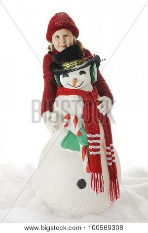 An elementary girl hiding behind a Christmas snowman while preparing to throw a snowball.  On a white background.
