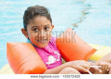 Cute Indian girl learning swimming in pool. Asian kid in swimmer class with float bands.
