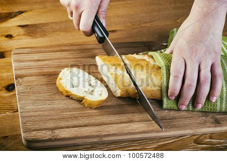 Woman's hands cutting bread on the wooden plank