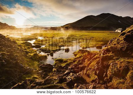Above the source of thermal water steam rises. White nights in Iceland. Sunrise Park Landmannalaugar