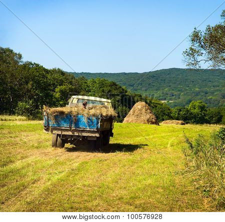 russian farmer riding old truck fully covered by hay