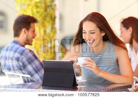 Happy Woman Watching Videos In A Tablet In A Coffee Shop