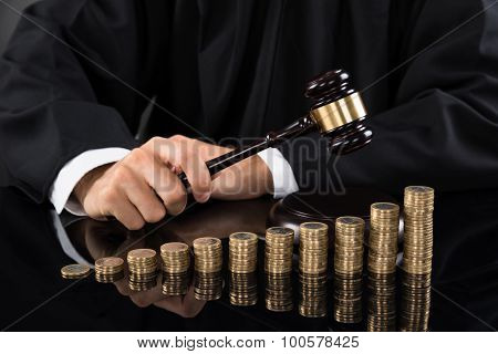 Judge Hitting Gavel In Front Of Coins