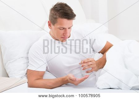 Man In Bed Taking Medicine
