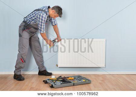 Male Plumber Repairing Radiator