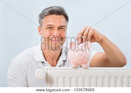 Man Inserting Coin In Piggy Bank