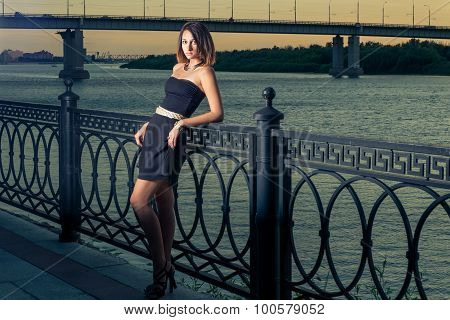 Fashion girl with is leaned back against metal fence