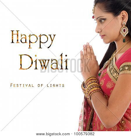 Indian woman in traditional sari praying and celebrating Diwali or deepavali, fesitval of lights at temple. Girl prayer hands folded, isolated on white background.