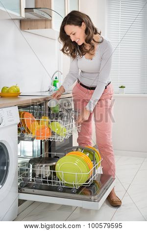 Woman Removing Cup From Dishwasher