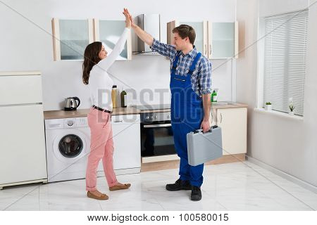 Woman Giving High Five To Repairman