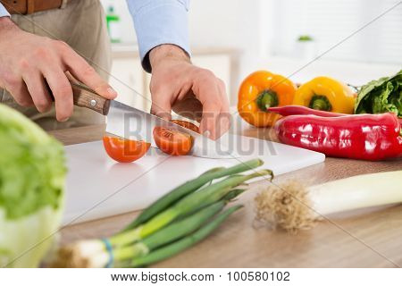 Male Hands Cutting Tomato At Countertop