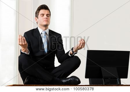 Businessman Sitting In Lotus Position At Desk