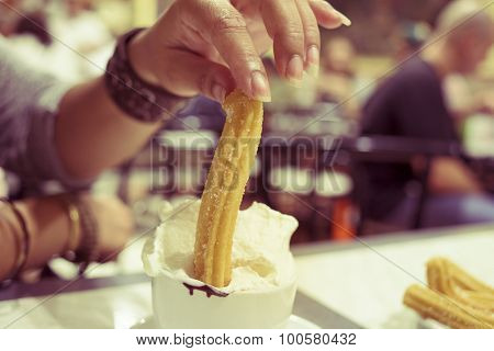 closeup of a woman soaking Spanish churros in a chocolate Suizo, a hot chocolate topped with whipped cream, in a cafe