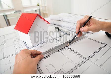 Engineer Drawing Diagrams On Blueprint
