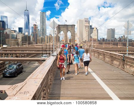NEW YORK,USA- AUGUST 20,2015 : Tourists at the Brooklyn Bridge with the Manhattan skyline on the background