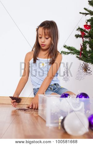 Happy little girl decorating a christmas tree