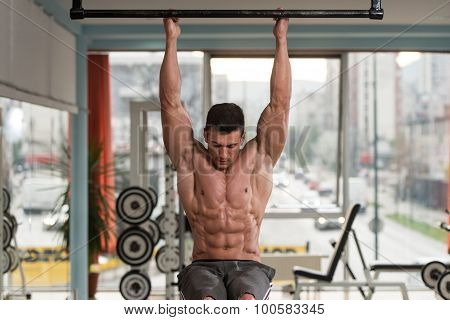 Young Man Performing Hanging Leg Raises Abs Exercise