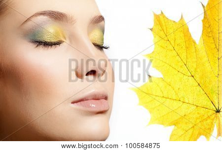 closeup portrait of attractive  caucasian  woman  isolated on white studio shot lips  face closeup makeup  head eyes closed skin yellow maple leaf autumn