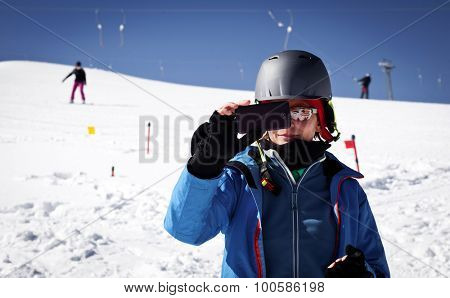 Woman taking photos with phone on ski slope - winter vacation