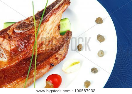fresh hot roasted beef meat bone steak on ceramic dish with red hot pepper and capers on blue wooden table