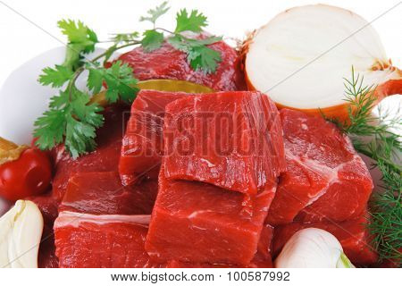fresh uncooked beef meat slices over white bowls ready to prepare with red peppers and greenery isolated over white background