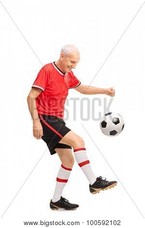 Full length portrait of a senior man in a red jersey juggling a football and smiling isolated on white background