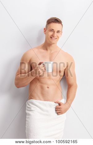 Vertical shot of a handsome man with a white bath towel around his waist holding a cup of coffee and looking at the camera