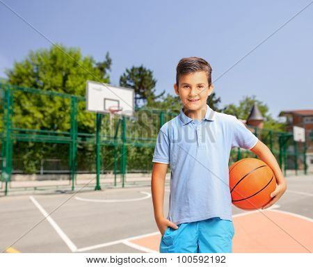 Joyful little boy in a blue shirt holding a basketball at an outdoor basketball court and looking at the camera