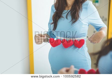 Asian Pregnant Woman With Heart Shape Accessories On Her Tummy