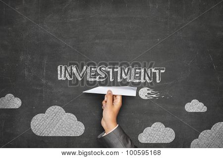 Investment concept on blackboard with paper plane
