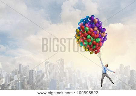 Young successful businessman flies on bunch of colorful balloons