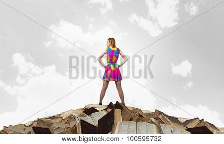 Woman in multicolored dress standing on pile of books