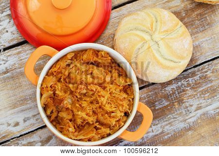 Polish bigos in saucepan and bread roll on rustic wooden surface