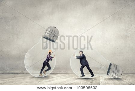 Businesswoman and businessman inside light bulb trying to get out
