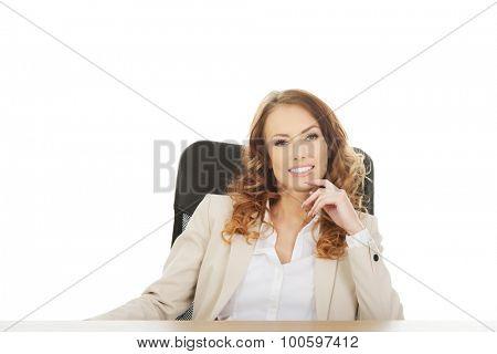 Happy businesswoman by a desk.
