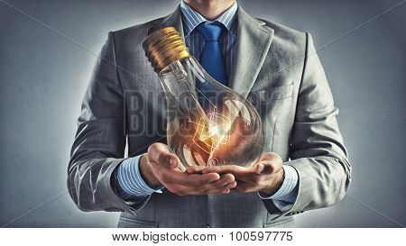 Young businessman presenting glass glowing light bulb in his hands