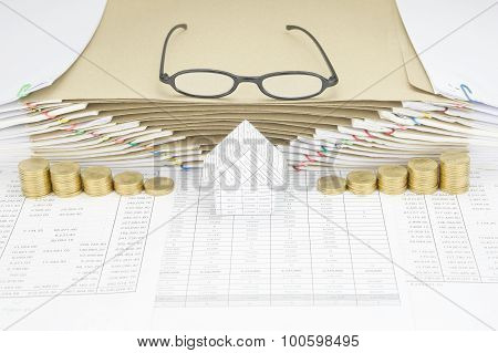 House Between Gold Coins Have Spectacles On Top Of Envelope